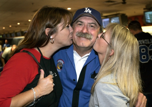 TALK03 102528 9/1/04 SAM RICHE / THE INDIANAPOLIS STAR:Q95's Bob Kevoian gets a smooch from fiance Becky Martin, left, and Kristi Lee, right and also at Q95. The second annual Peyback Bowl hosted by Peyton Manning and held to benefit Peyton Manning's foundation, was held at Woodland Bowl on East 96th street on the northside of Indianapolis on Wednesday evening, September 1, 2004.